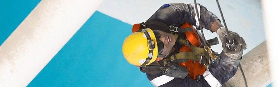 Aerial view of man working in safety gear climbing scaffolding